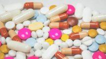 Pílulas de diversas cores sobre uma mesa.
