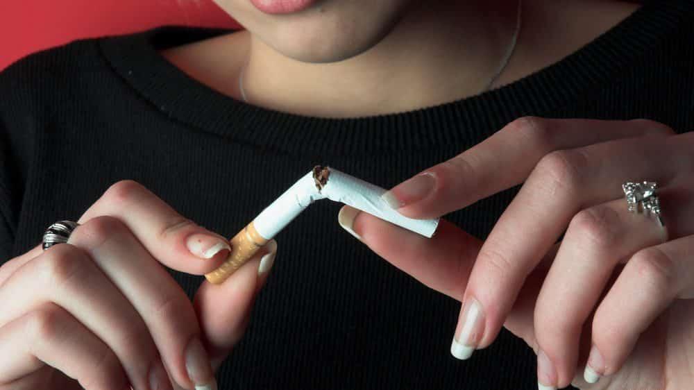 Close de mãos de mulher partindo um cigarro ao meio. mulheres têm mais dificuldade para largar o cigarro.