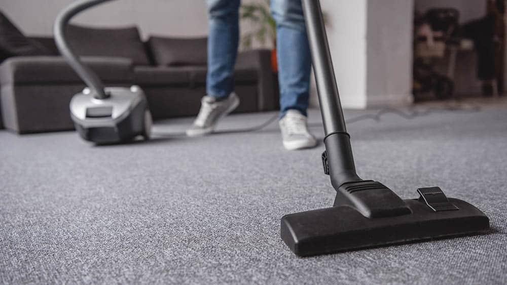 Pessoa passando aspirador de pó no carpete.