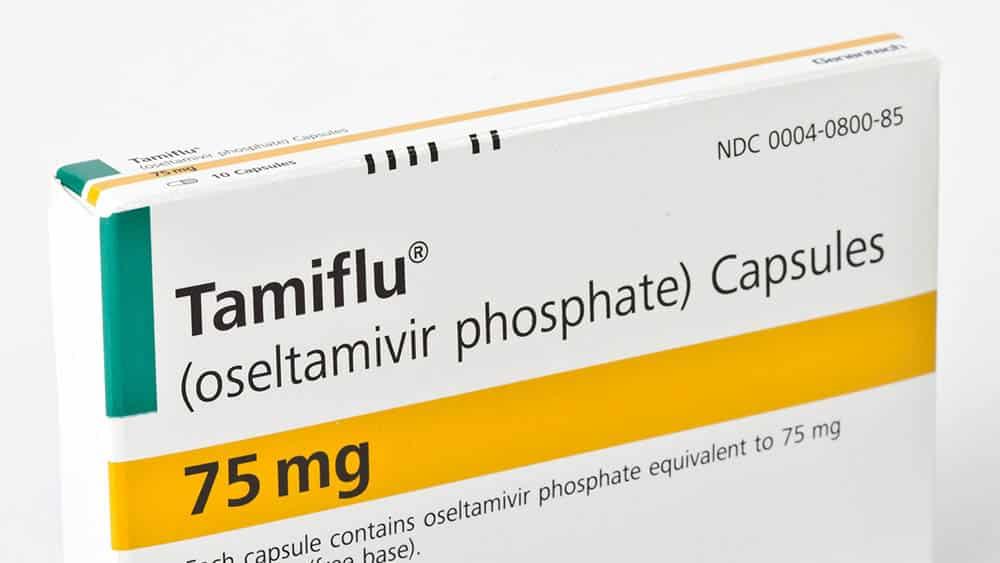 Detalhe de uma caixa do medicamento Tamiflu sobre um fundo branco.