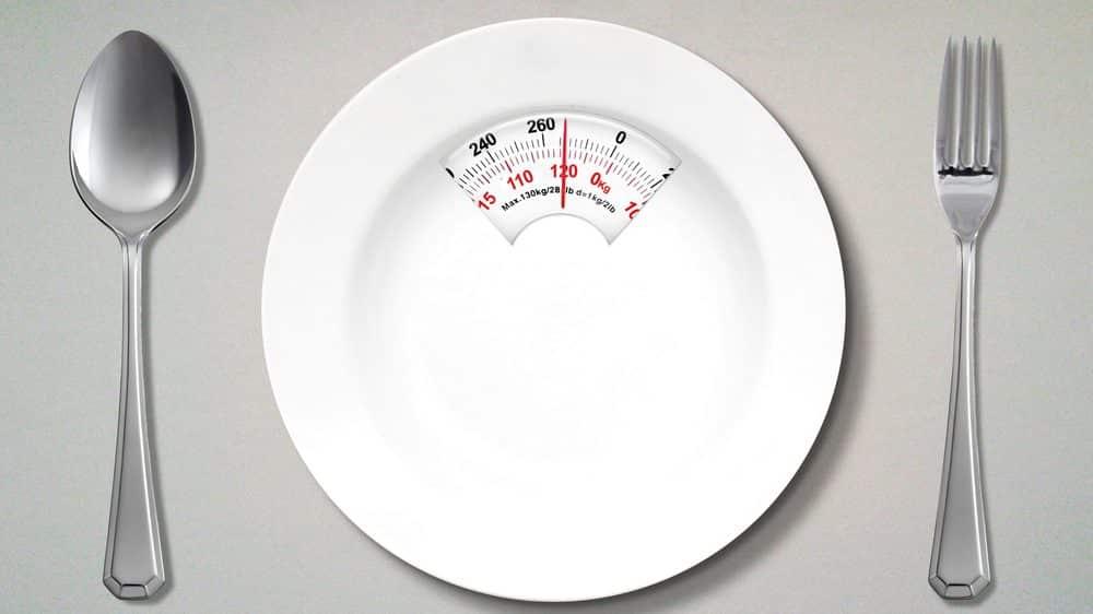 prato vazio, com marcador de peso, ladeado por garfo e faca. veja histórico da obesidade