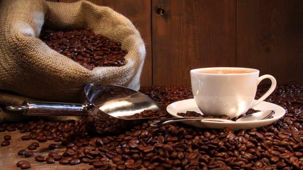 xícara com café em grão e saco de café ao lado. café pode ajudar a reduzir doenças no fígado