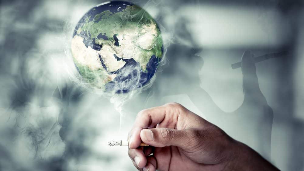 mão de homem segurando cigarro com fumaça envolvendo globo terrestre. número de fumantes no mundo ainda é alto