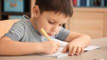 Menino escrevendo em caderno.