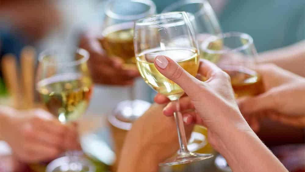 Mãos brindando com taças de champanhe, com mão de mulher em primeiro plano.