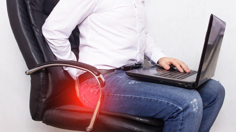 homem sentado, segurando computador no colo, com sinal de dor no ânus. Ficar muito tempo sentado aumenta risco de hemorroidas.