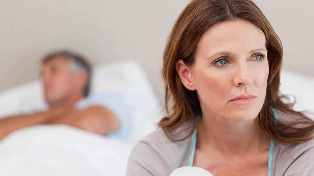 Mulher triste com marido deitado na cama desfocado ao fundo.