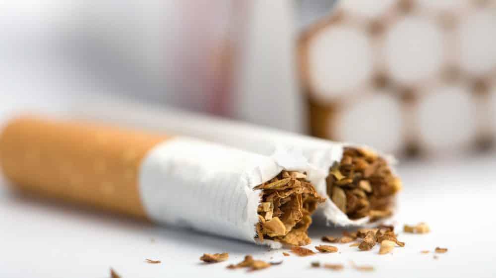 close de cigarro quebrado ao meio sobre a mesa. nicotina é considerada porta de entrada para outras dorgas
