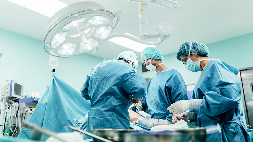 Três médicos operando em uma sala de cirurgia, local mais sujeito a ocorrências de sepse.
