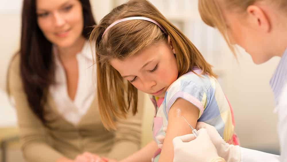 Menina sendo vacinada e mãe observando ao fundo.