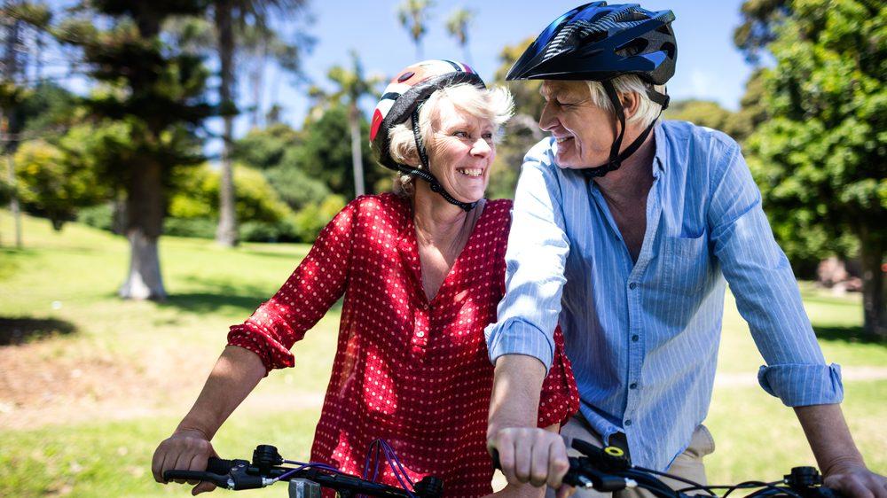 casal de idosos sorri ao andar de bicicleta. exercícios físicos reduzem risco de depresão