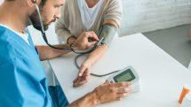 Enfermeiro aferindo a pressão arterial de uma paciente.