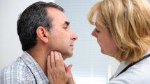 Médica examinando a garganta de paciente.