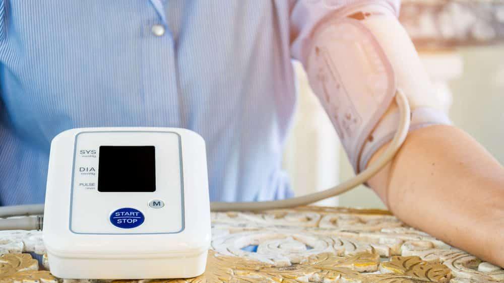 mulher medindo a pressão em aparelho em casa