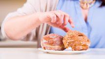 mão estendida para alcançar prato de rosquinhas. obesidade mundial tem crescido