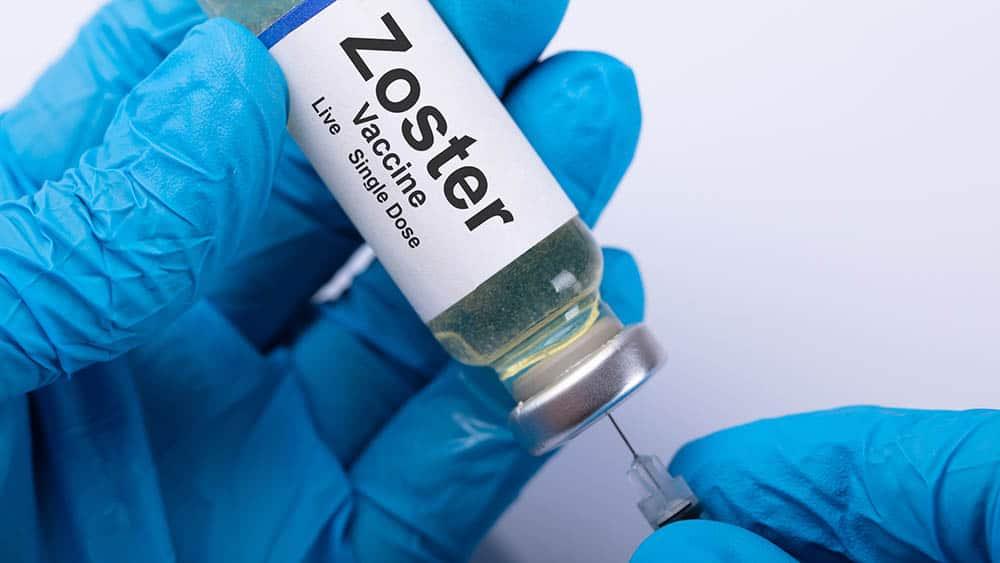 Mãos com luva azul enchendo uma seringa com vacina contra o herpes-zóster.