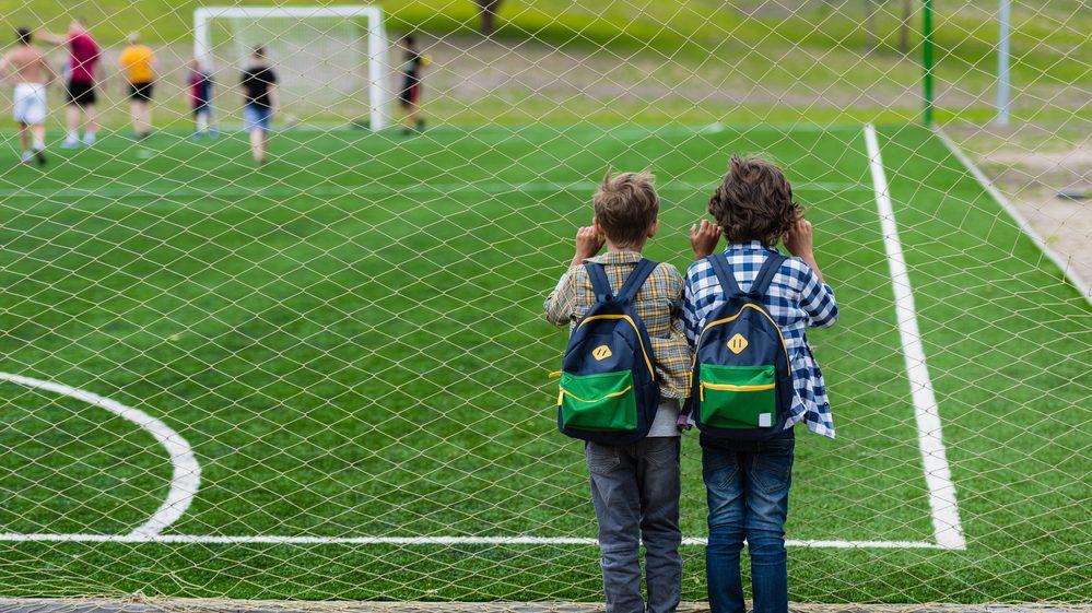 dois meninos de costas, assistem à partida de futebol próximos á rede. cosme e damião eram amigos desde a infância