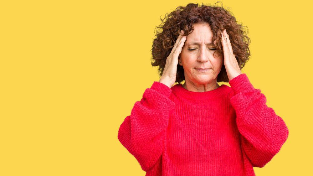 Mulher sofre com dor de cabeça