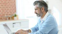 Homem grisalho trabalhando no computador.