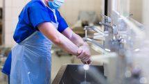 Médico com avental lavando as mãos antes de cirurgia.