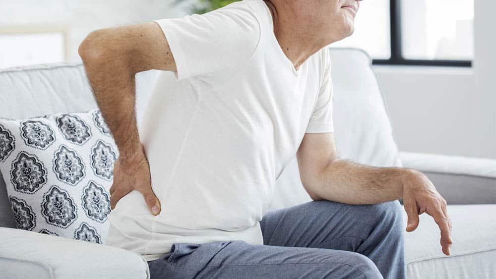 Homem sentado com a mão no final das costas e expressão de dor.