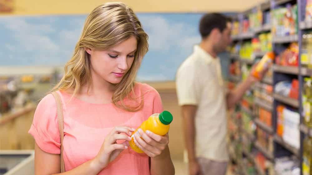 Mulher em supermercado lendo rótulo de um suco em garrafa.