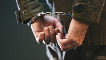 homem com mãos para trás, algemado. é preciso distinguir melhor usuário e traficante de drogas