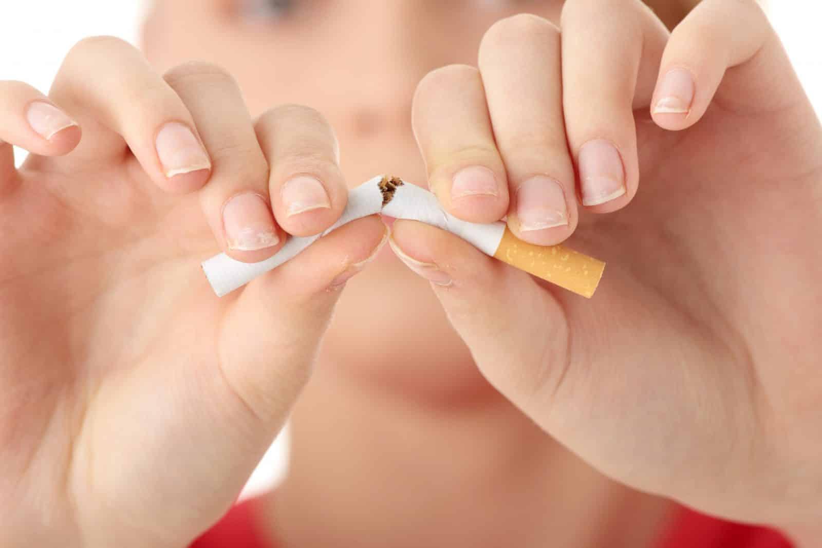 Mãos quebrando um cigarro ao meio.