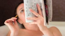 Mulher deitada fazendo palavras cruzadas, um dos melhores exercícios para o cérebro.