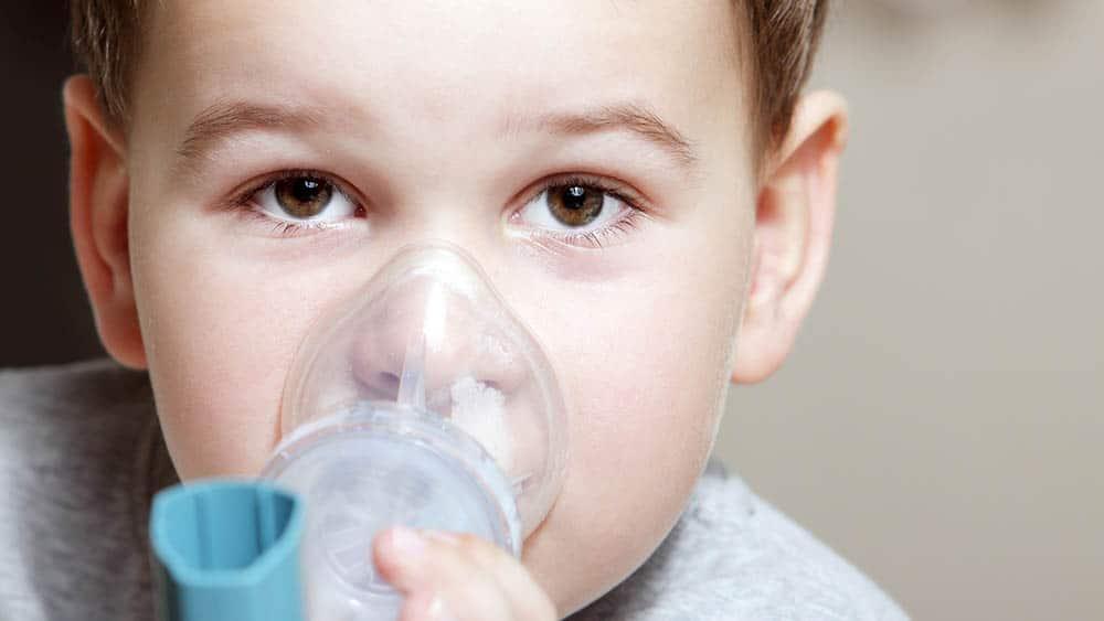 Menino pequeno fazendo inalação.. veja relação entre higiene e asma