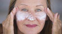 Mulher mais velha passando protetor solar nas maçãs do rosto.