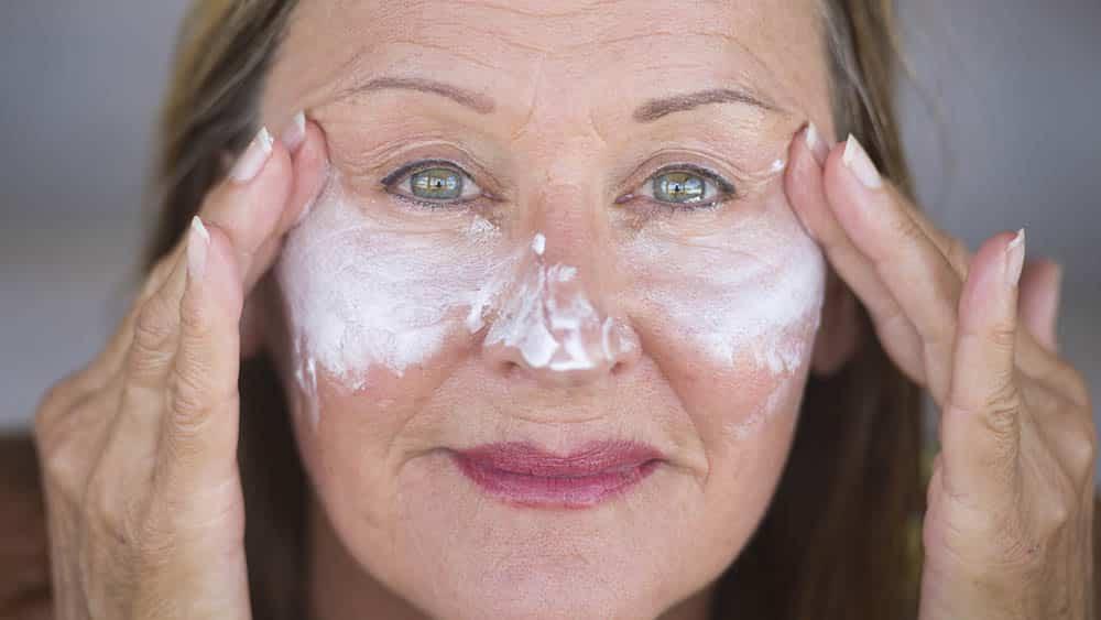 Mulher mais velha passando protetor solar nas maçãs do rosto para evitar problemas causados pelo lúpus e exposição solar.