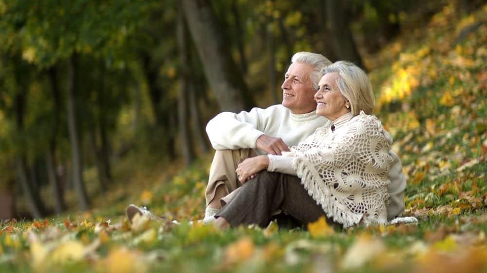 casal de idosos sentados em gramado do parque; estudo sobre longevidade mostra que envelhecer não é sinônimo de adoecer