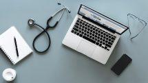 Computador, estetoscópio, bloco de notas, caneta, copo de café e óculos de grau em uma mesa. artigo sobre os visionários do SUS