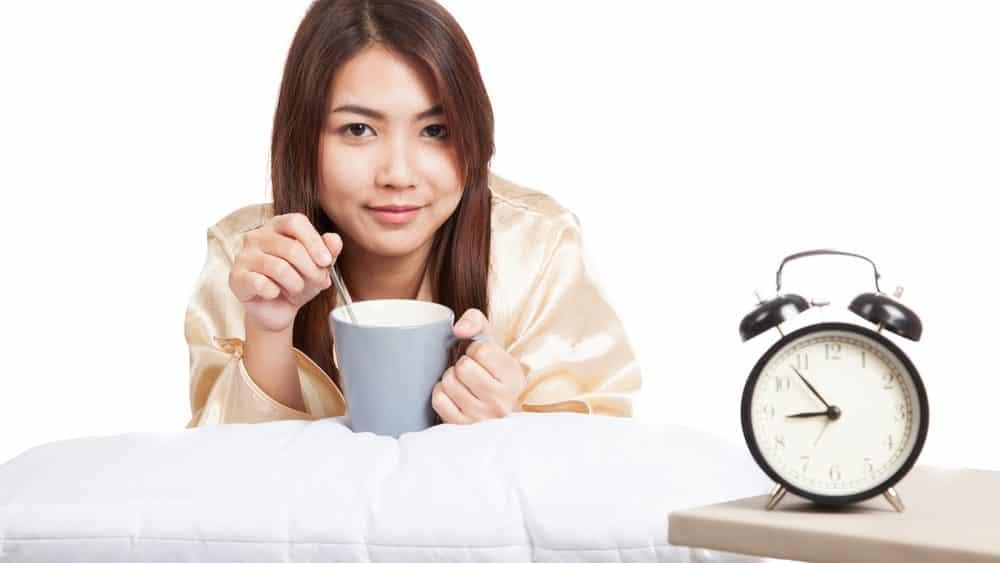 moça deitada diante de despertador com xícara de café. café interfere no sono