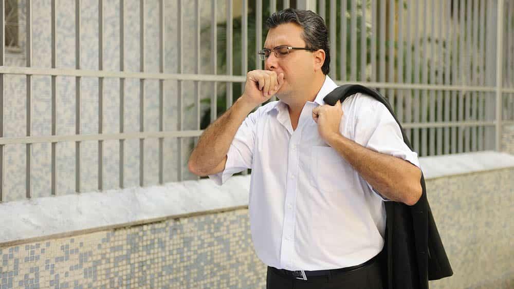 Homem tossindo com mão na boca enquanto caminha pela rua.