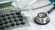 estetoscópio e calculadora sobre uma mesa indicando os altos custos da saúde
