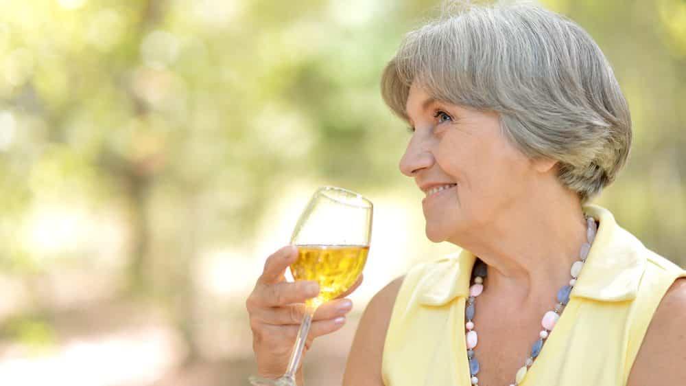 idosa feliz, com taça de vinho na mão. Veja a história de dona Ana.