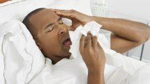 Homem com gripe deitado e espirrando.