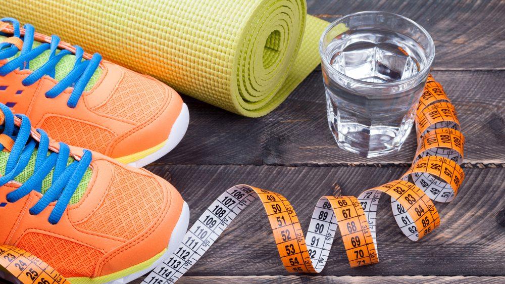 par de tênis, tapete de ioga, copo de água e fita métrica. Há relação entre estilo de vida e câncer