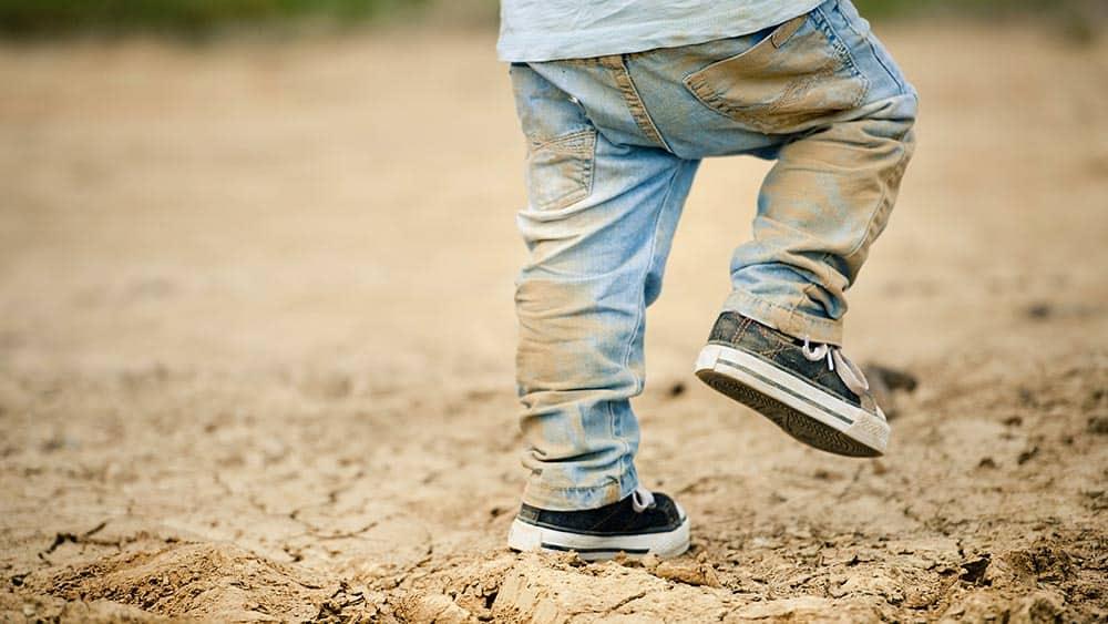 Menino brincando em chão de terra com jeans sujo.