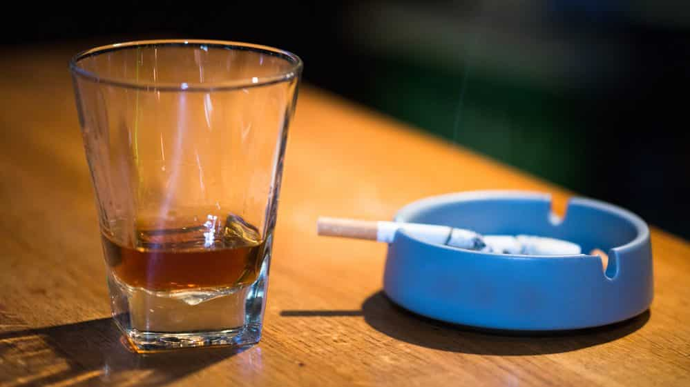 copo de bebida alcoólica e cigarro queimando no cinzeiro. neurobiologia das drogas ajuda a explicar dependência química