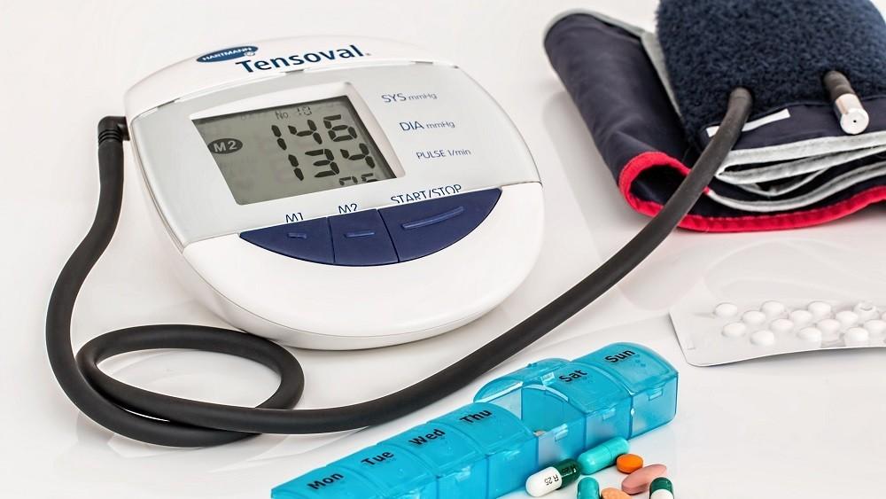 Aparelho de pedir pressão e medicamentos sobre uma mesa.