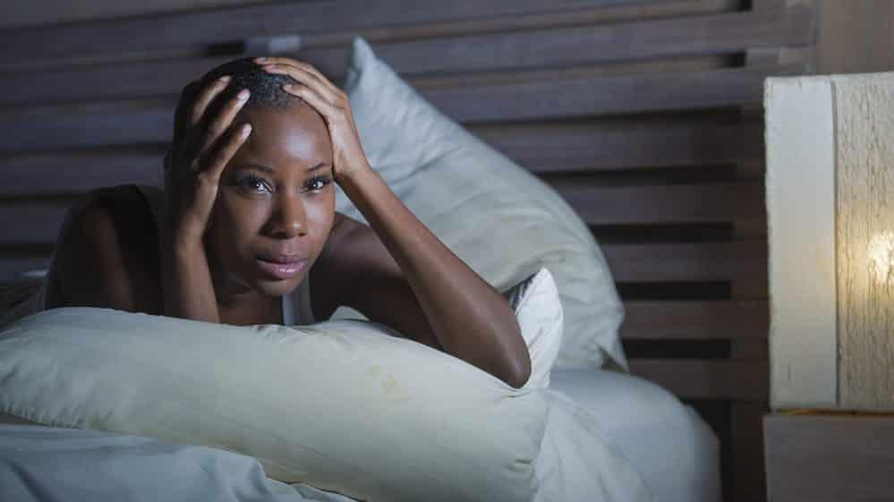 mulher deitada com insônia crônica, com mãos na cabeça
