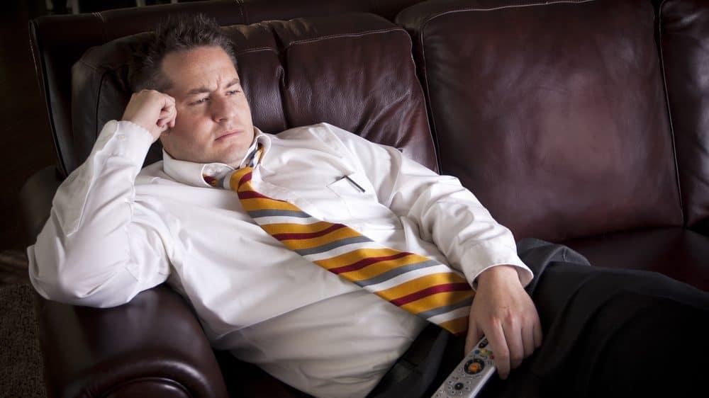 homem de gravata deitado no sofá, com controle remoto na mão, assistindo à TV. A vida sedentária está associada a várias doenças