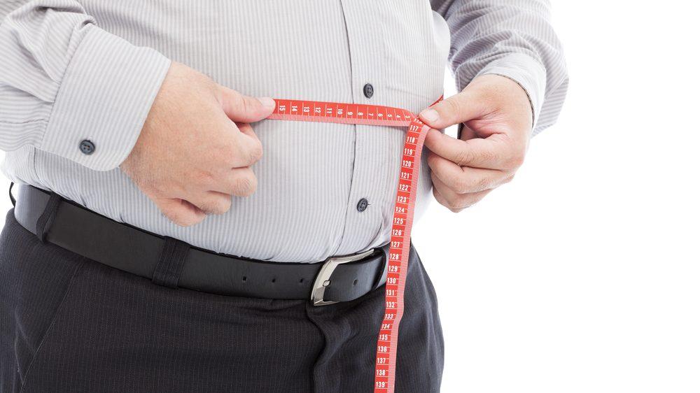 homem com excesso de gordura na cintura mede a região com fita métrica