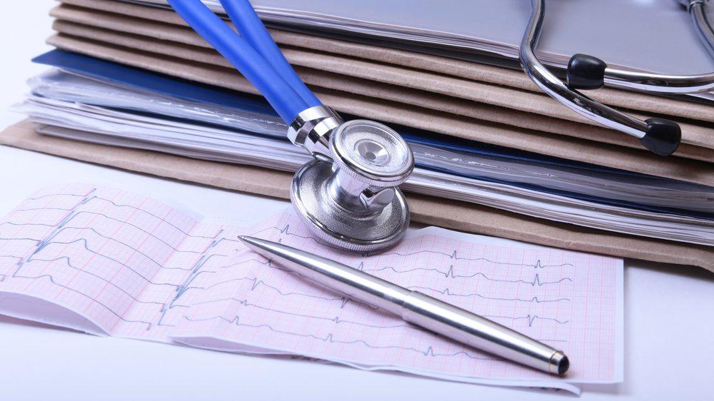 pilha de pastas com exames. estetoscópio e caneta. Excesso de exames onera sistema de saúde