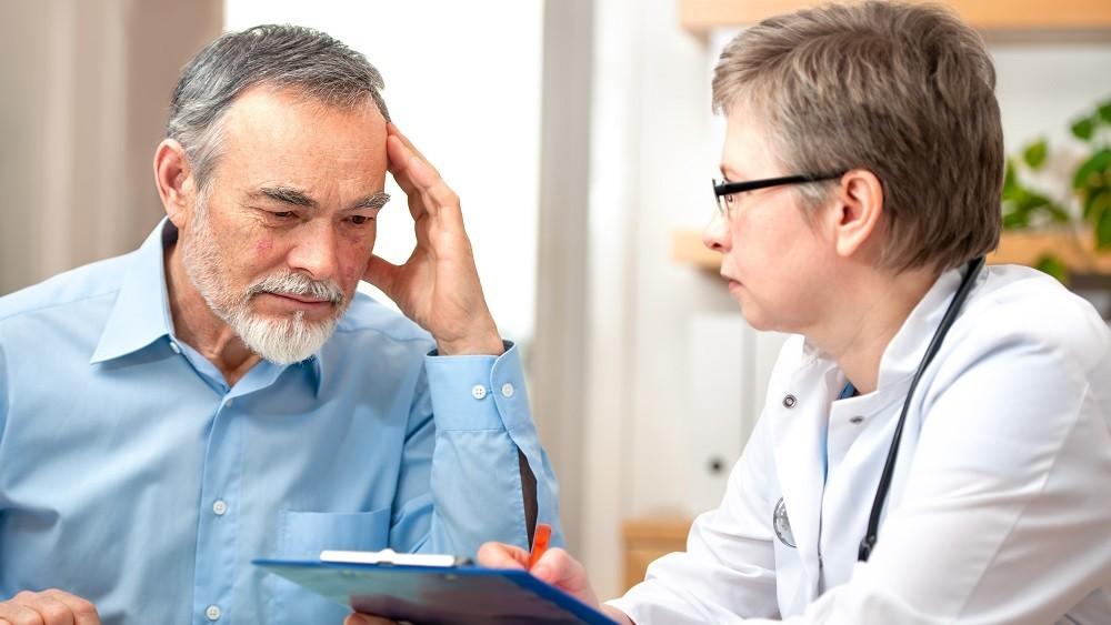 Médica conversando com paciente homem.