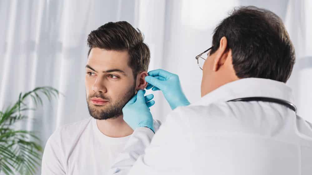 médico remove cerume de ouvido de paciente