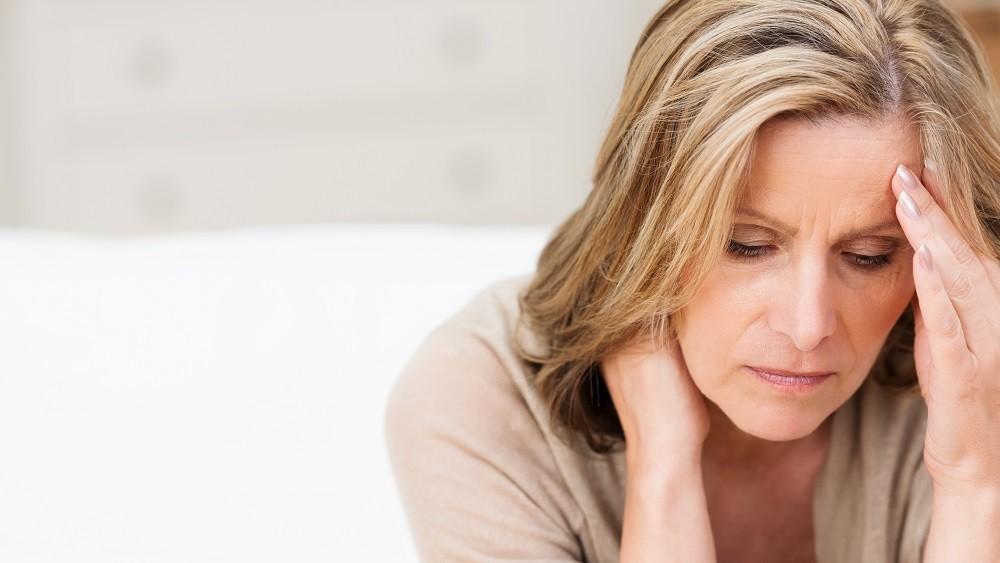 Mulher sentindo desconforto. menarca precoce influi na menopausa precoce